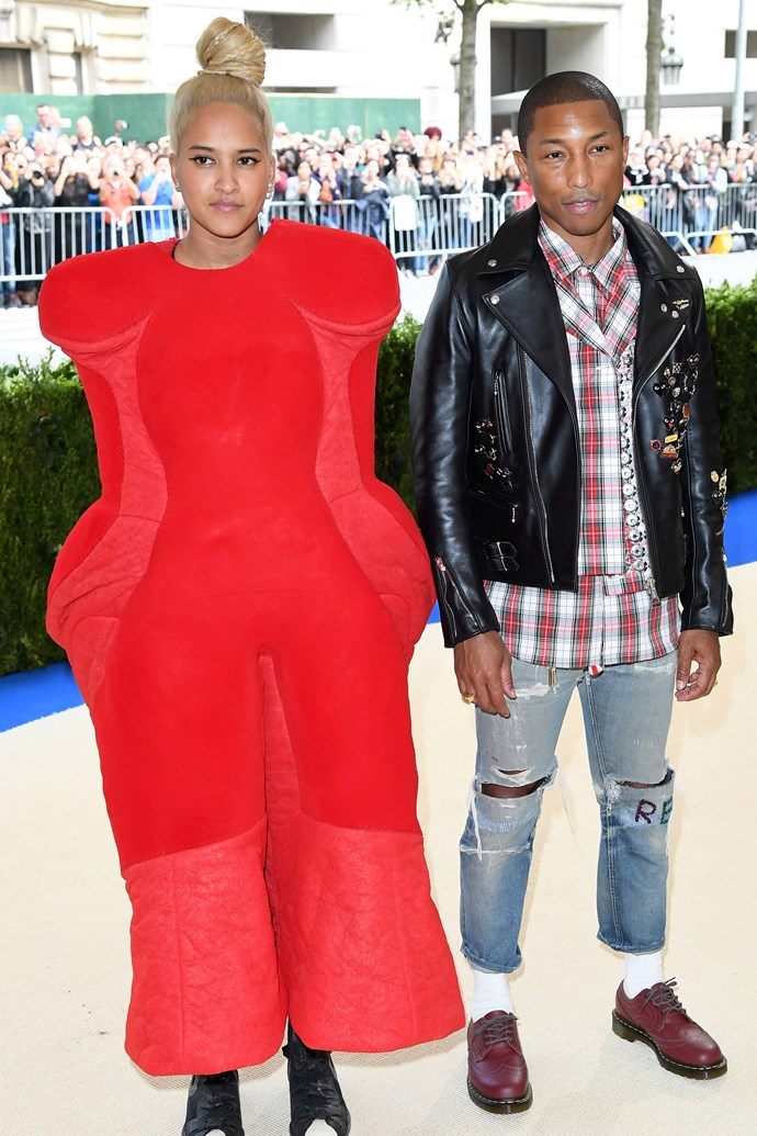 **2017: HELEN LASICHANH in Comme des Garçons** <br><br> Pharrell's wife Helen Lasichanh sacrificed limb mobility in favour of an iconic sartorial moment at 2017's *Comme des Garçons*-themed gala.  <br><br> Lasichanh looked the perfect contradiction to her husband's relaxed Chanel get-up, and, as one of the first arrivals, the twosome set the tone for the bevy of fashion moments to come later in the evening.