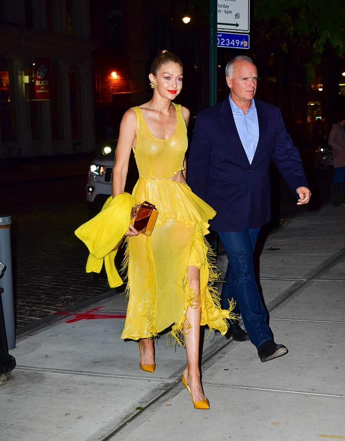 ***Add a bright lip***<br> Gigi might be wearing a yellow fringed dress, mustard pumps, a patchwork clutch and a yellow sweater, but our eyes are drawn to her bright orange lip. A lesson in expert distraction, courtesy of Ms Hadid.
