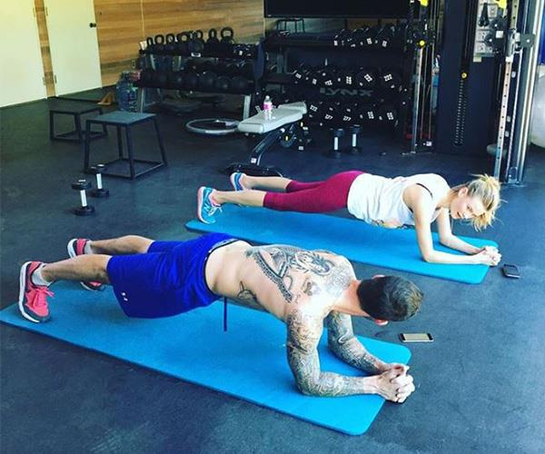 """Kinda have a thing for my trainer,"" Behati Prinsloo captioned this pic of her and husband Adam Levine holding the plank position."