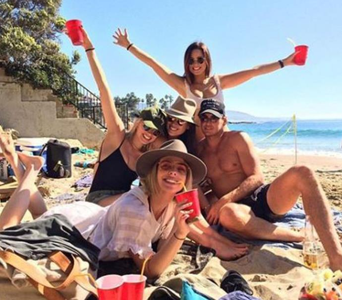 **February 2017:** Robbie (left, middle row) wearing her favourite black one-piece again, but this time with a more casual olive-green cap, round-frame sunglasses and denim shorts while relaxing at the beach with friends in California. (Image: Instagram)