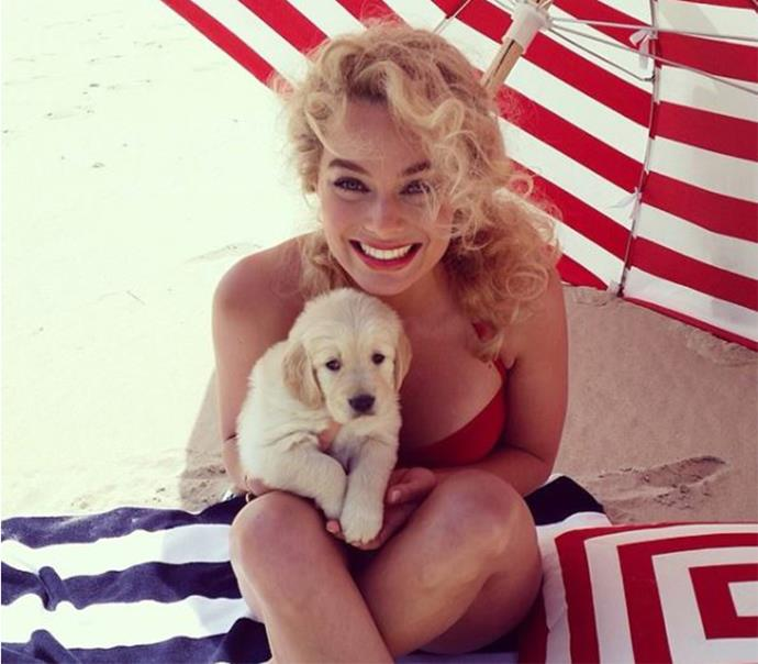 **July 2014:** While shooting for *Vanity Fair*, Robbie wore a '50s look, matched her lipstick to her swimsuit and coordinated her hair colour with her puppy. (Image: Instagram)
