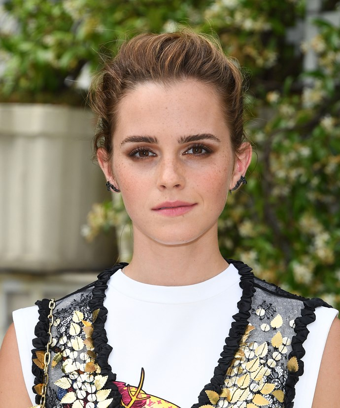 A messy up-do, paired with a bronze smokey eye and nude lips complements Emma's edgy outfit at an event in Paris in 2017.