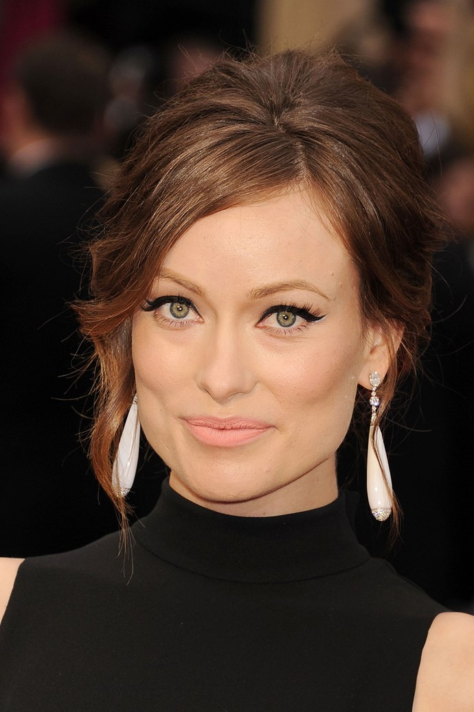 Wilde pairs an elegant up-do with winged eyeliner and a peach lip at the 2014 Academy Awards.