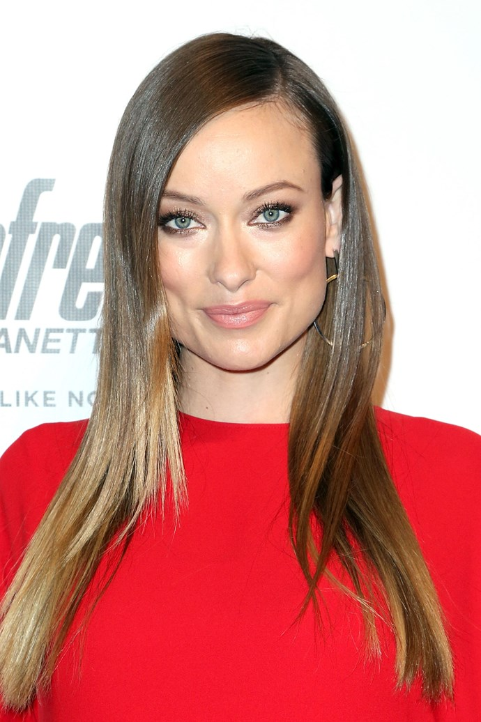 Wilde complements her red body-con dress with a neutral smokey eye and glowing complexion at an event in 2016.