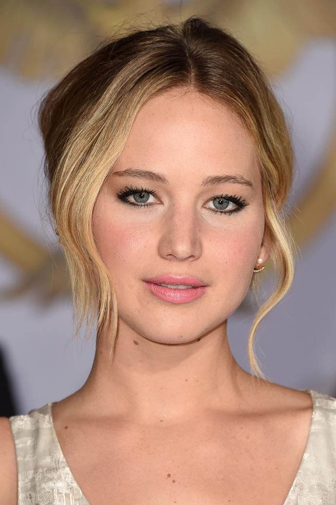 Jennifer wears a messy bun with natural makeup and a baby pink lip at the premiere of *The Hunger Games: Mockingjay—Part 1* in 2014.