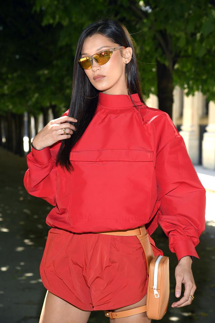 Bella Hadid favours streamlined sunglasses, a fanny pack and a windcheater while attending the Louis Vuitton Menswear show at Paris Fashion Week.  *Photo: Getty*