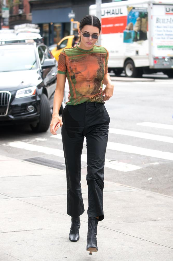 Kendall Jenner in a sheer printed t-shirt and black trousers, September 7th, 2018.