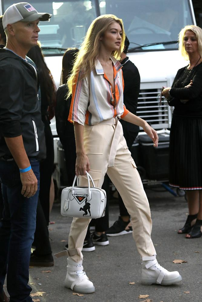 Gigi Hadid in cream pants and a striped button-up, September 7th, 2018.