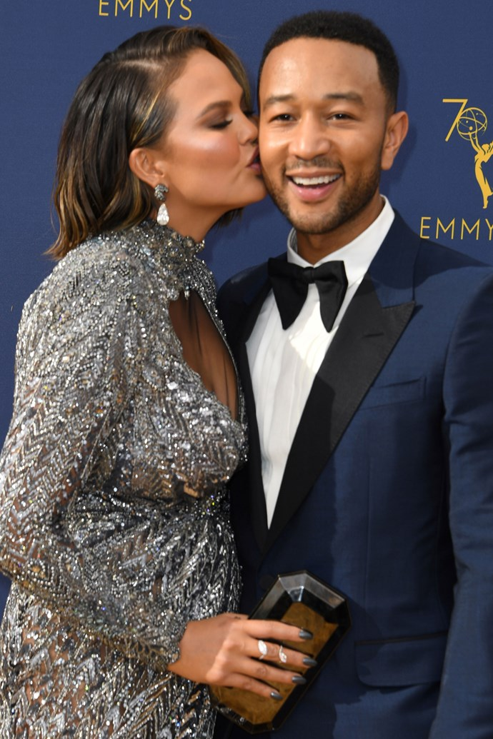 Chrissy Teigen and John Legend. <br><br> Being the loved-up couple that they are, they put on quite the display of PDA while walking the red carpet, Teigen planting a kiss on Legend's cheek.