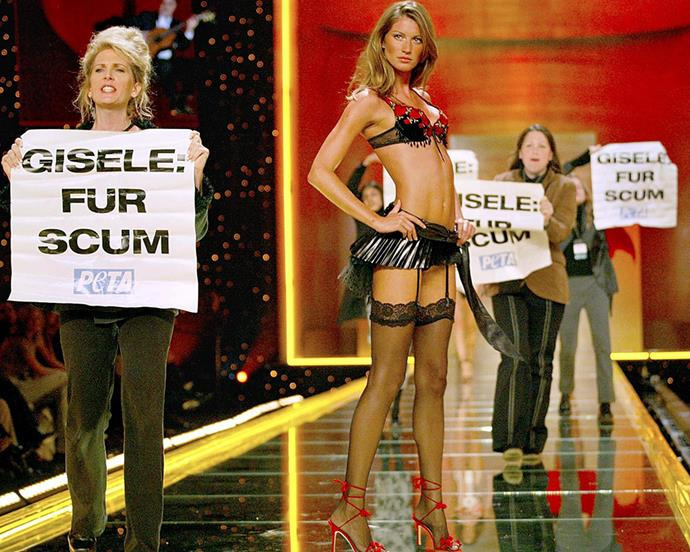 "***2002: PeTA protesters crashing the stage*** <br><br> At the 2002 show, four protesters leaped on stage during Gisele Bündchen's runway walk carrying banners that read ""GISELE: FUR SCUM"", before they were hastily yanked from the catwalk by security.  <br><br> Amid the chaos, someone managed to snap this picture of Bündchen posing amid the protesters, which somewhat resembles a renaissance artwork."