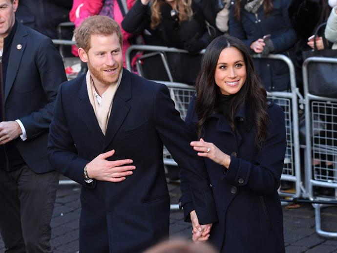Performing their signature move, here Harry clutches onto Meghan's hand while she places her other hand on his shoulder.