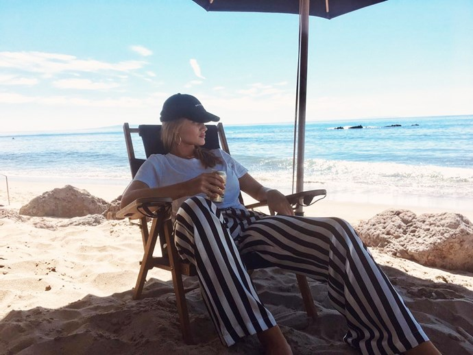 *Striped silk pants and a baseball cap*<br><Br> For unparalleled beach-side cool, just look to Rosie Huntington-Whiteley. Her version of beach attire rests on luxe silk pants in a black-and-white stripe, a classic white tee, and a baseball cap. Strip off to a nude bikini but keep the gold hoops on for your mid-afternoon dip.