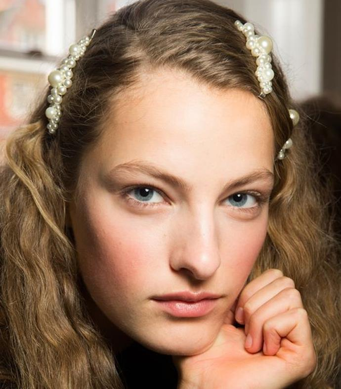 **Twisted Half-Up** <br><br> **Runway:** Simone Rocha's models carried soft curls pinned back with pearled clips.