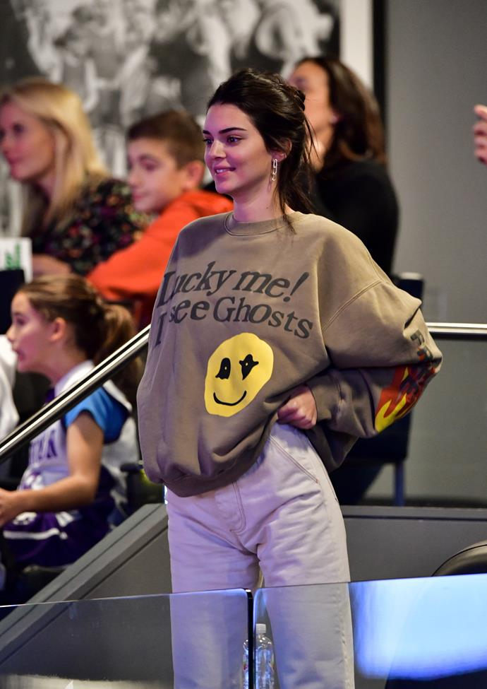 Kendall Jenner dons an oversized novelty jumper from Cactus Plant Flea Market's Kanye West x Kid Cudi capsule collection and baggy mom jeans to watch rumoured boyfriend Ben Simmons play basketball.