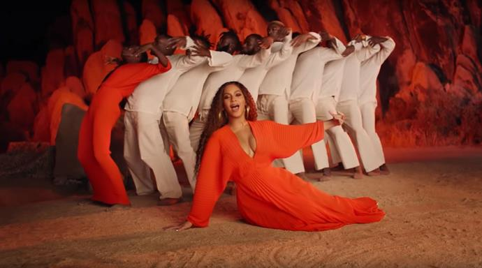 The songstress closed the video in a bright orange pleated dress with a plunging neckline.