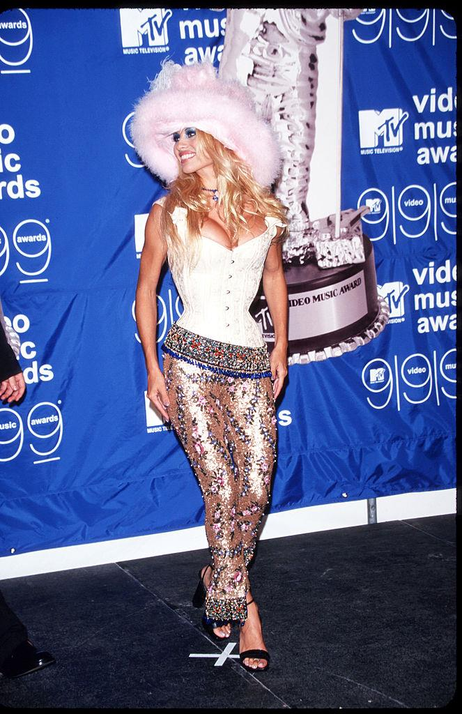 **Pamela Anderson's feathered hat and corset in 1999**<br><br>  Sporting feathers, a corset and sequins, Pamela Anderson's 1999 get-up is a mainstay in the 'outrageous VMAs looks' hall of fame.