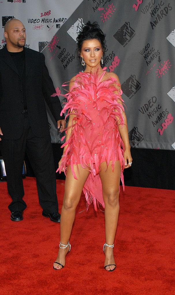 **Christina Aguilera's hot pink feather look in 2003**<br><br>  Pairing a fierce tan with even fiercer feathers, Christina Aguilera showed up and showed out at the 2003 awards.