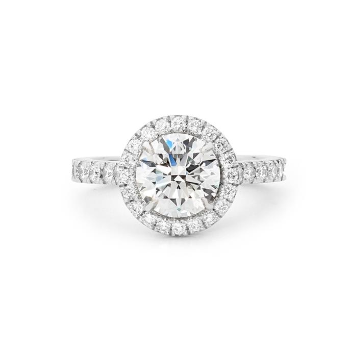 "Diamond halo ring, POA by [Matthew Ely](https://www.matthewely.com.au/products/2-06ct-round-brilliant-cut-halo-diamond-engagement-ring/6285/?terms=43|target=""_blank""