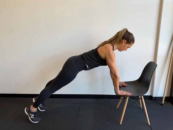 **Chair Supported Plank Hold**<br><br>  Place both hands on your chair (or the edge of your desk) and hold a high plank position. Your feet should be shoulder width apart. Tuck your pelvis forward so your glutes are not piked.<br><br>   *Hold for 60 seconds*