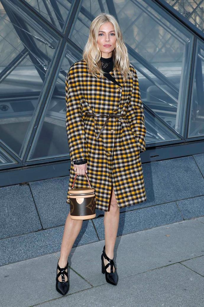 In a Louis Vuitton coat and dress.