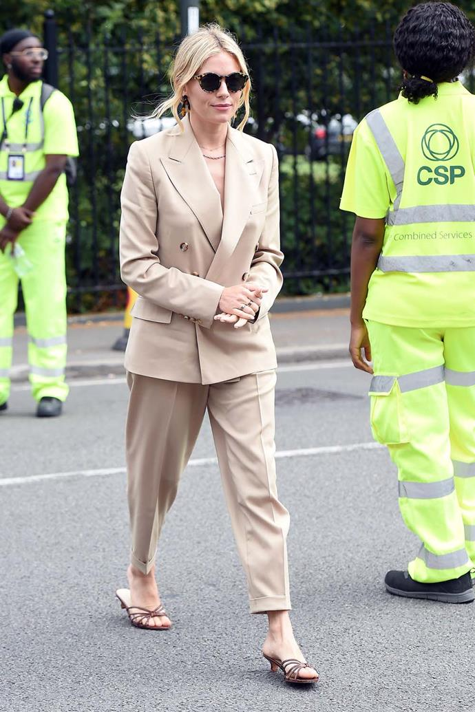In a sand-coloured suit and kitten heels.