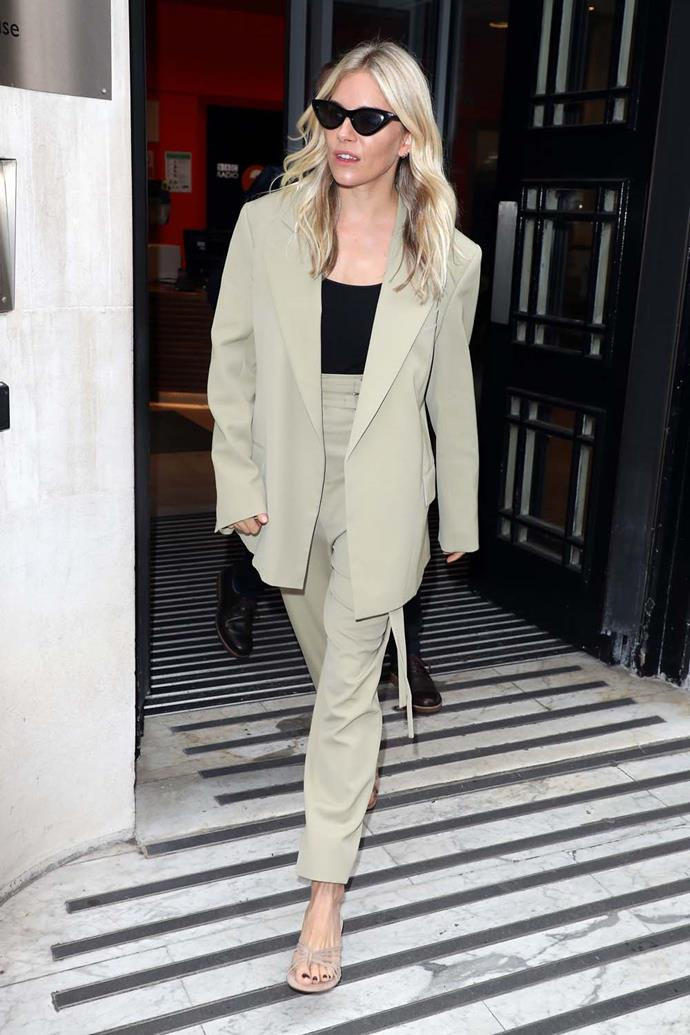 In a pistachio suit with nude sandals.