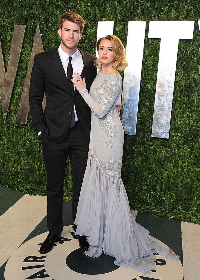 With her ex-husband, Liam Hemsworth, at the *Vanity Fair* Oscar Party in 2012. <br><br> *Image: Getty*