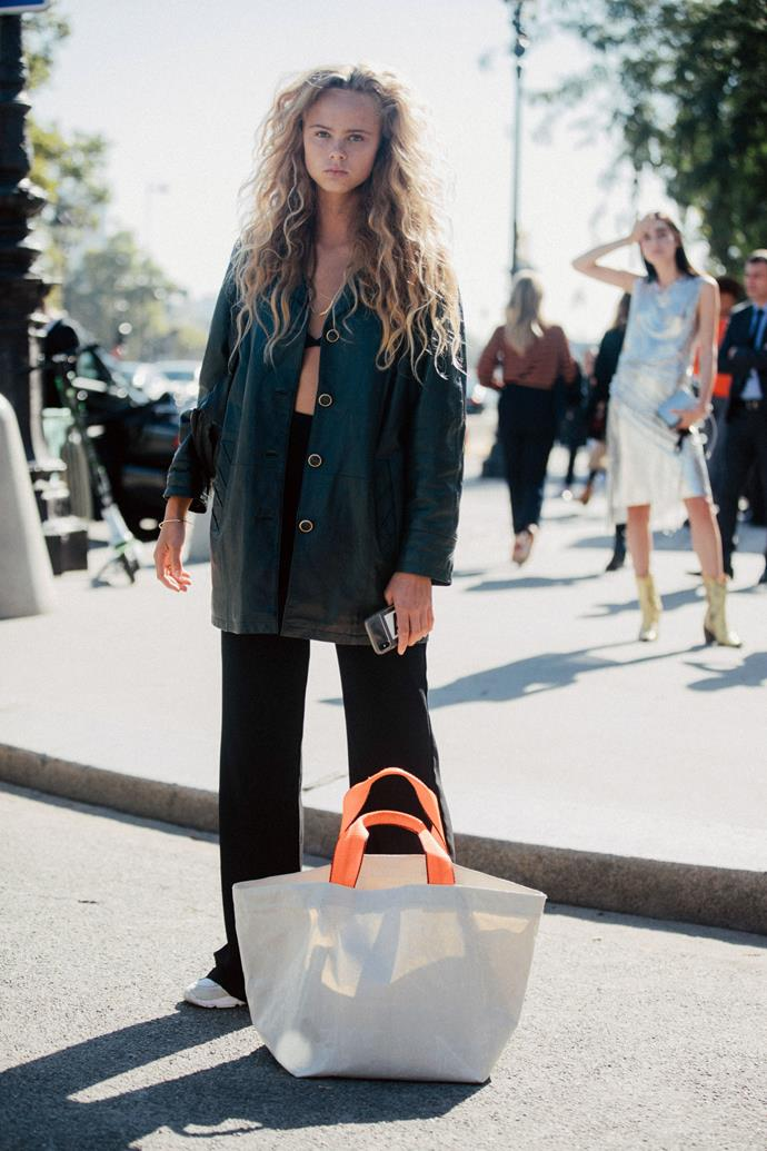 Embrace summer 2020's bikini-top-as-clothing trend but keep it subtly sexy by layering an oversized linen shirt over loose-fitting black pants.