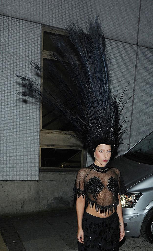 Lady Gaga in a giant feathered headpiece arriving at *The Graham Norton Show* in October 2013.
