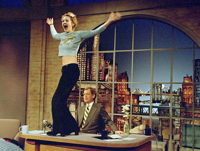 Drew Barrymore in a cropped long-sleeved t-shirt, flared trousers and black pumps on *The Late Show with David Letterman* in April 1995.