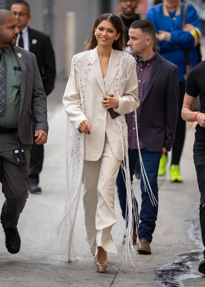 Zendaya in a white blazer and netted cape arriving at *Jimmy Kimmel Live* in May 2019.