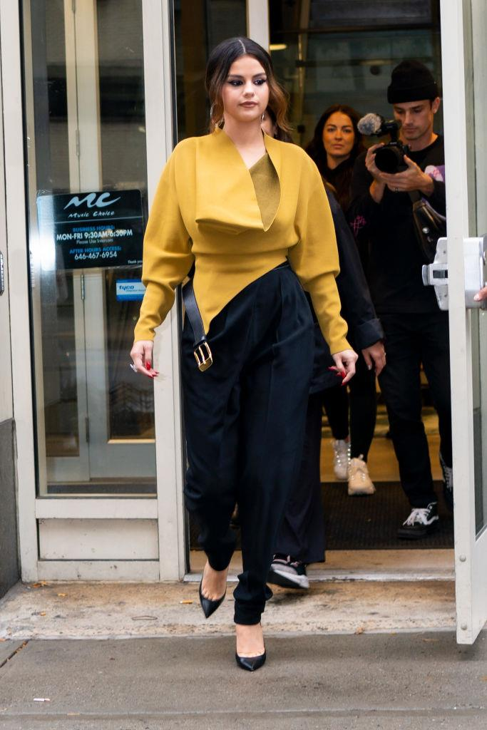 In tapered pants and a mustard-toned top on October 29, 2019.