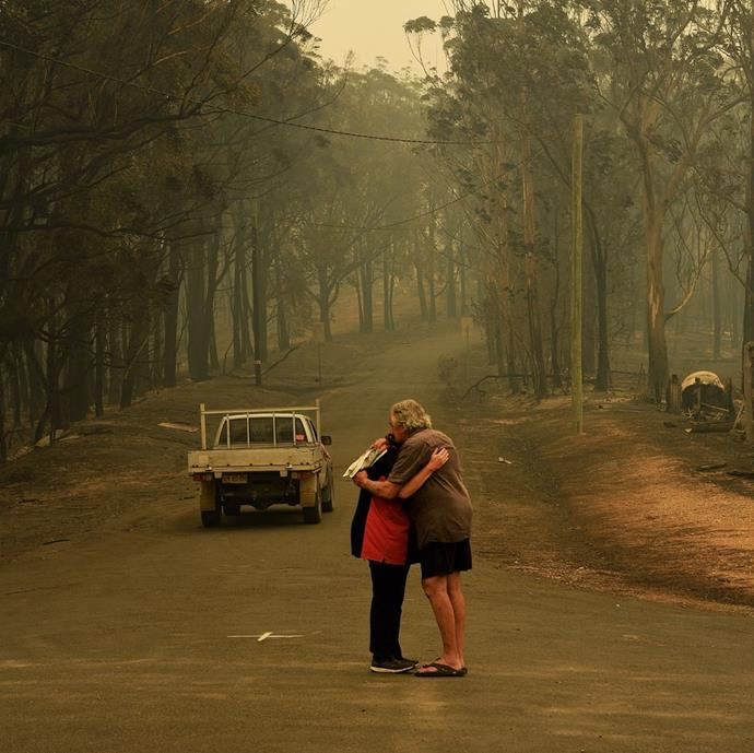 "**Kate Geraghty, *Sydney Morning Herald* Staff Photographer** <br><br> ""This image taken on January 1 is of two residents in Nelligen, NSW, embracing in the street the morning after their town was hit by the Clyde Mountain Fire. Several properties were lost. <br><br> To me it summed up the momentary relief of surviving this fire as the town came under threat again several days later. It also shows the typical Australian country community where everyone knows everyone and they look out for each other. It was a fleeting moment taken on the way to a property on the outskirts of town by a couple who lost their home. We have seen these scenes play out all over our country in the past two months as communities brace for more to come."" <br><br> *Image: Kate Geraghty/*Sydney Morning Herald"