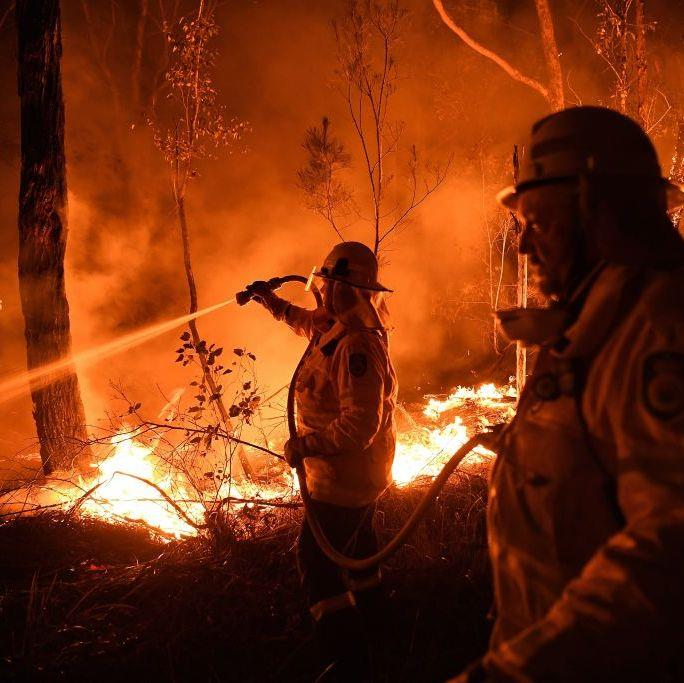 "**Kate Geraghty, *Sydney Morning Herald* Staff Photographer** <br><br> ""On New Year's Day, leading up to another series of catastrophic bushfire days, myself and *Sydney Morning Herald* journalist Peter Hannam were sent to monitor and cover the Clyde Mountain Fire that grew from the Currowan Fire and is still to this day burning out of control. <br><br> We have training which allows us access through roadblocks and entry to fire grounds with fire and rescue crews to report immediately from the fire fronts. This fire has been burning for weeks. Every day and night, fire crews have been fighting and monitoring different fire fronts that appear from this fire. It continues to burn, so this scene shown in the photo is what is happening all across the fire ground. <br><br> Fire crews and locals continue to carry out property protection. These crews worked through the night to have a couple hours rest before returning home to their area to prepare for catastrophic conditions the following day. I hope, in this image, you see the bravery of our firefighters and their selfless dedication to protecting us. I also hope it is a reminder of how volatile and dangerous these fires are and to heed the warnings to evacuate and or have a proper fire plan."" <br><br> *Image: Kate Geraghty/*Sydney Morning Herald"