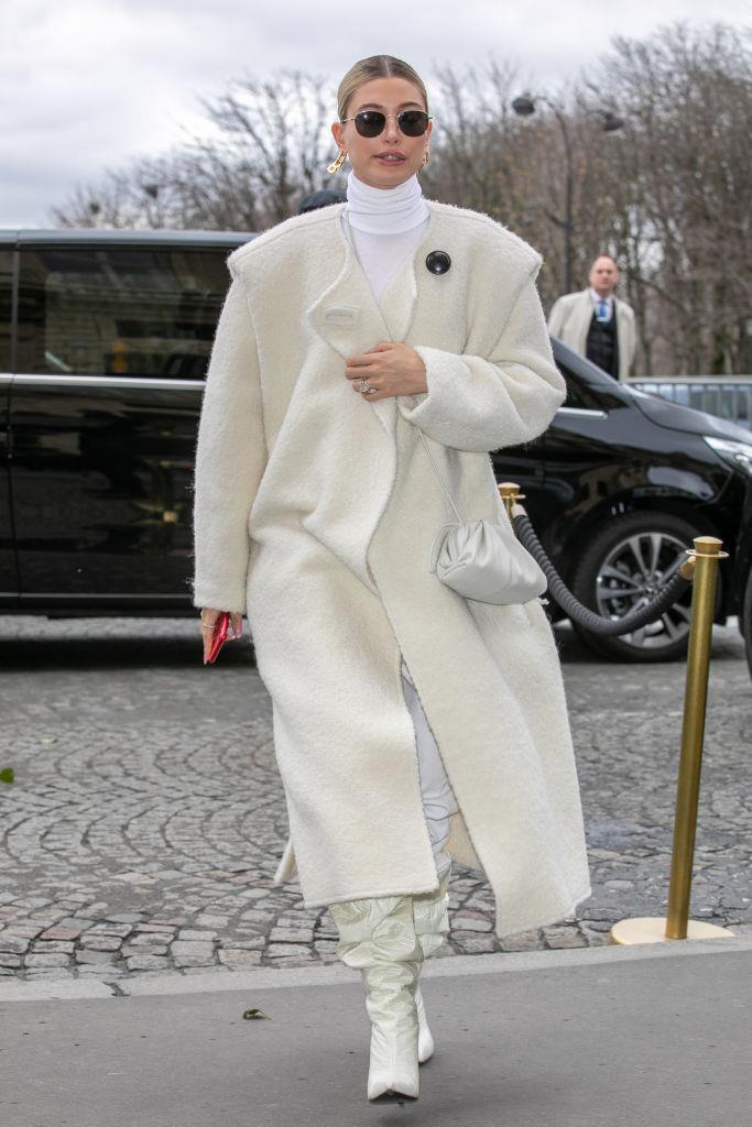 In an Isabel Marant coat, Fenty boots, and carrying a miniature Bottega Veneta 'Pouch' bag.