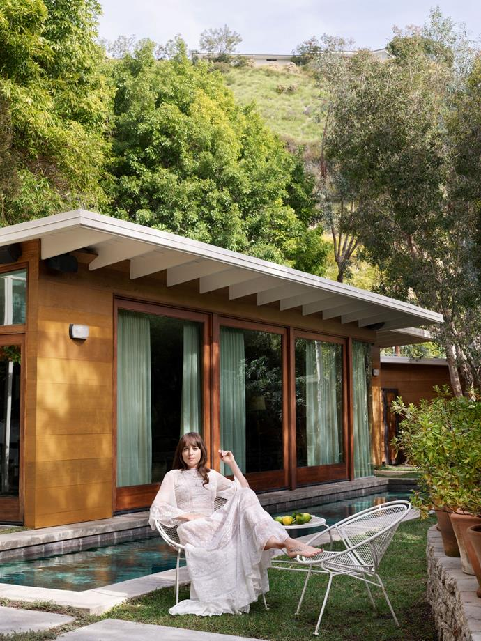 """Johnson in her courtyard, in front of the lap pool. <br><br> *Image by Simon Upton for [Architectural Digest](https://www.architecturaldigest.com/story/step-inside-dakota-johnsons-midcentury-modern-home