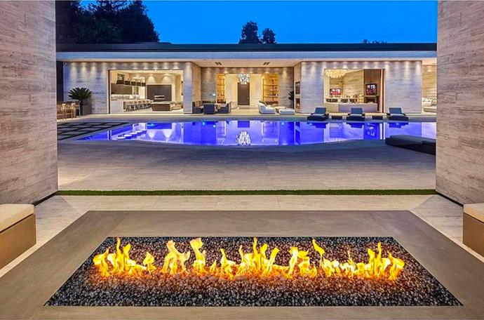 """The outdoor fireplace, perfect to warm up during moonlight movie nights with the outdoor projector. <br><br> *Image by [MLS/Zillow](https://www.zillow.com/homedetails/145-N-Mapleton-Dr-Los-Angeles-CA-90077/20523926_zpid/? target=""""_blank"""" rel=""""nofollow"""").*"""