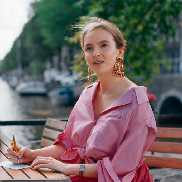 **Villanelle from *Killing Eve*** <br><br> *The Oversized Shirt* <br><br> While her career choice isn't exactly traditional, Villanelle's wardrobe certainly is. Wearing a pink oversized shirt tied at the waist, she elevates the casual look with a giant pair of gold, statement earrings.