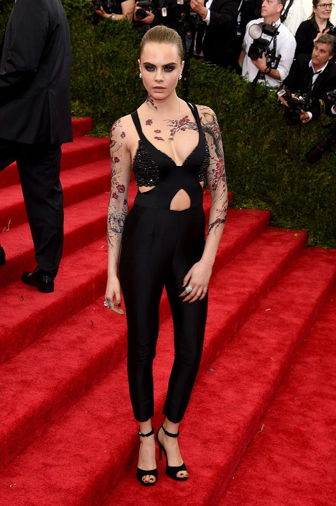 """**Cara Delevingne in Stella McCartney (2015)** <br><br> By some accounts, you could call Cara Delevingne's fitted McCartney pantsuit a 'casual' choice. However, the real art was her temporary tattoo bodywork, featuring handiwork from revered tattoo artist, [Bang Bang](https://www.elle.com.au/celebrity/cara-delevingne-tattoo-18859