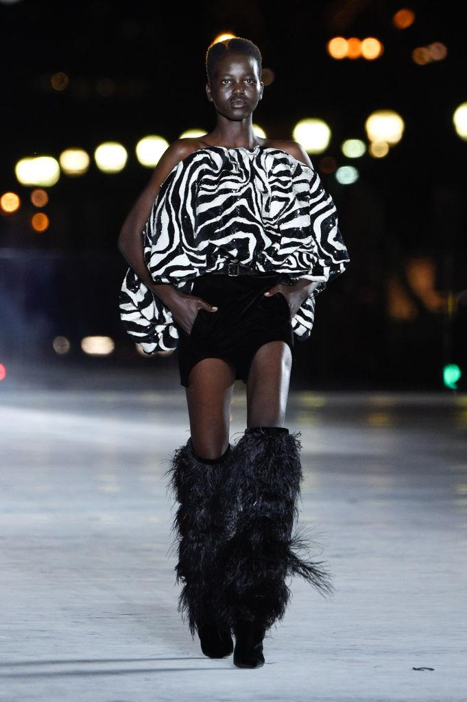 """**Adut Akech walking for Saint Laurent spring/summer '18** <br><br> Supermodel-in-the-making Adut Akech had her big break walking at Saint Laurent's spring/summer '18 show when she was 17 years old. The show was her Paris Fashion Week debut, and marked the beginning of an illustrious career for the Adelaide-based former refugee (Akech's family lived between South Sudan and Kenya before they arrived in Australia when she was a child). Since then, Akech has walked for the likes of Valentino, Isabel Marant, and Chanel, where she was even a '[Couture Bride](https://www.harpersbazaar.com.au/fashion/chanel-couture-brides-16877 target=""""_blank"""")' for the late Karl Lagerfeld."""