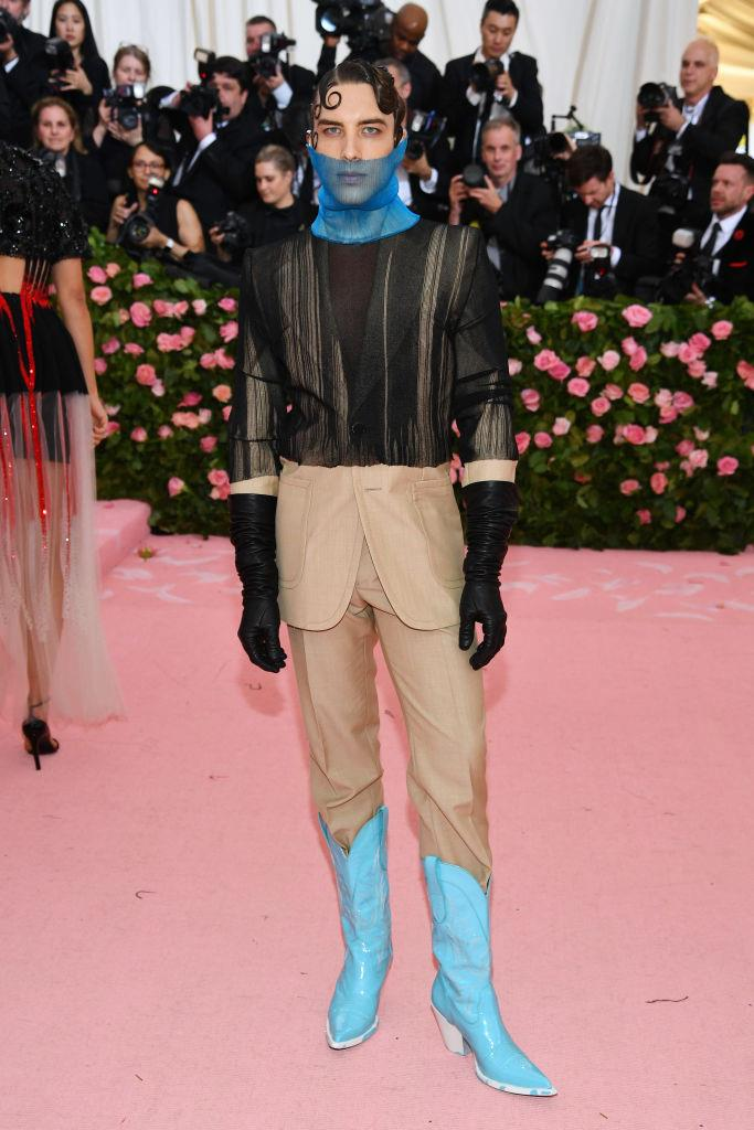 """**Cody Fern in Maison Margiela at the 2019 Met Gala** <br><br> Australian actor Cody Fern made headlines with his sleek, sheer outfit at the [2019 Golden Globes](https://www.elle.com.au/fashion/golden-globes-2019-red-carpet-19606 target=""""_blank""""), but the *American Horror Story* star one-upped himself in this conceptual Margiela ensemble (complete with neon-blue cowboy boots) at the 'Camp'-themed Met Gala during the same year. Thus, a fashion force was born."""