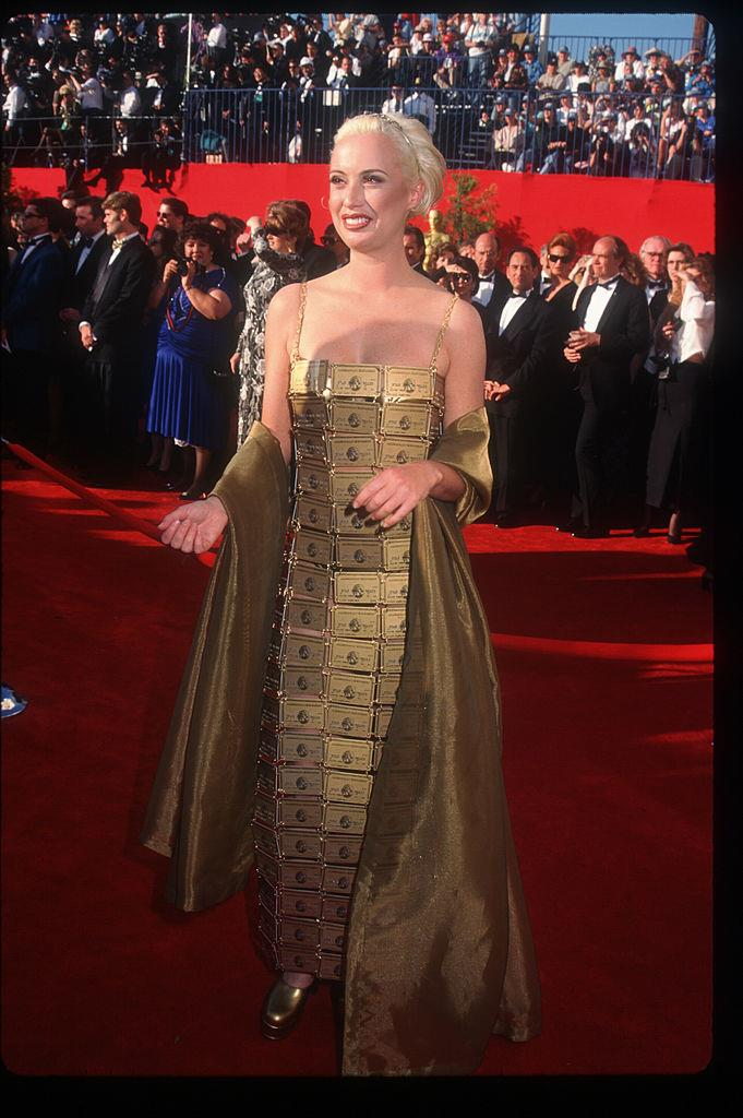 """**Lizzy Gardiner in her own design at the 1995 Academy Awards** <br><br> In the year she won an Oscar for her work in the film *Priscilla: Queen of the Desert*, costume designer Lizzy Gardiner wore this head-turning custom gown made out of gold American Express cards (all of which had her name on them). Though it's since been recognised as iconic, Gardiner has said she copped criticism for the look when she first wore it, with some Oscars viewers believing she """"wasn't taking things as seriously as [she] should""""."""