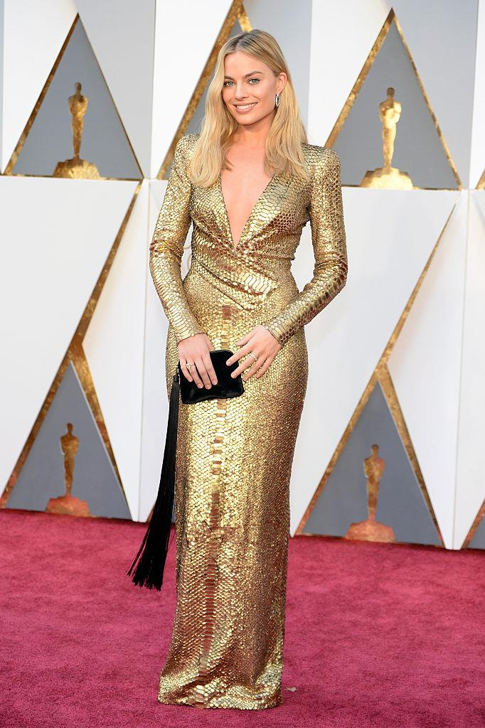 """**Margot Robbie in Tom Ford at the 2016 Academy Awards** <br><br> Though she was already an established Hollywood star by 2016, this outfit was arguably the one that started Margot Robbie's style streak. Her slinky, snakeskin-effect Tom Ford gown at that year's Oscars, paired with a black tassle-adorned clutch, represents everything we've come to love about the *[Bombshell](https://www.harpersbazaar.com.au/culture/bombshell-movie-plot-19819 target=""""_blank"""")* actress's style—chic, effortless and never trying too hard."""