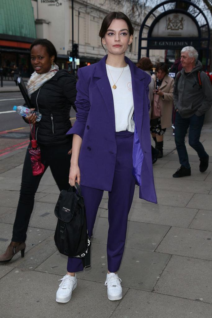 Actress Emma Mackey embraces her *Sex Education* character with a backpack to accessorise an electric blue suit.