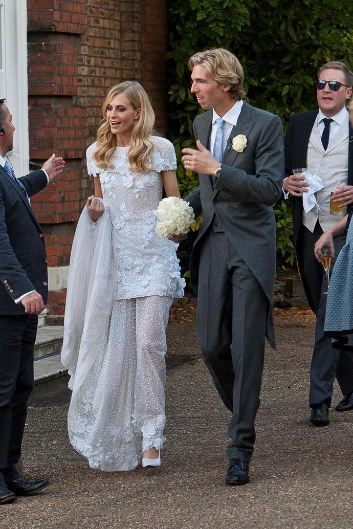 Poppy Delevingne wearing a mini wedding dress with a translucent skirt by Chanel in 2014.