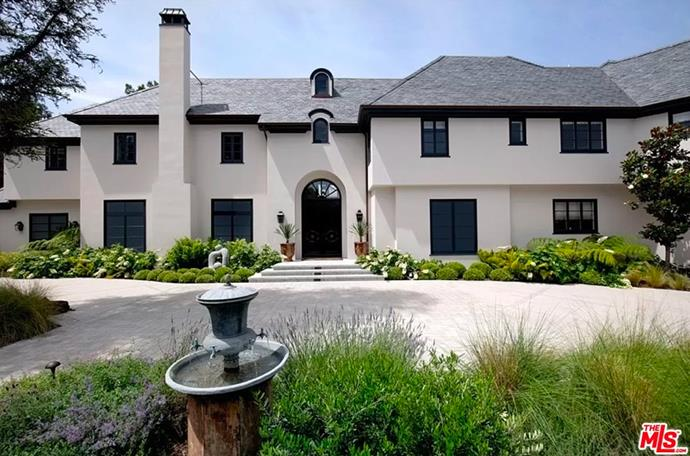 """The entryway to the home fitted with an arched doorway and a fountain. <br><br> *Image by [MLS/Zillow](https://www.zillow.com/homedetails/8-Beverly-Park-Beverly-Hills-CA-90210/20533668_zpid/?