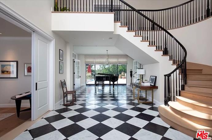 """The foyer including a sweeping staircase, grand piano and black-and-white checkered tiles à la Dorothy Draper. <br><br> *Image by [MLS/Zillow](https://www.zillow.com/homedetails/8-Beverly-Park-Beverly-Hills-CA-90210/20533668_zpid/?