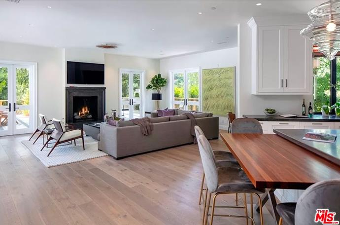 """The informal living room fixed with a wall-mounted television. <br><br> *Image by [MLS/Zillow](https://www.zillow.com/homedetails/8-Beverly-Park-Beverly-Hills-CA-90210/20533668_zpid/?