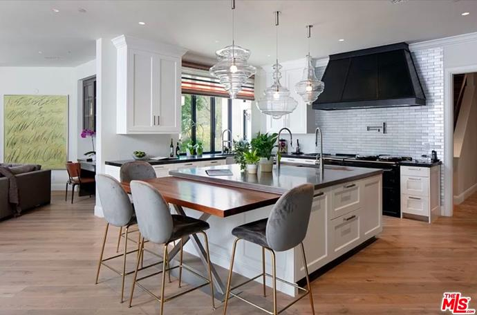 """The open plan kitchen and mini dining space, including unique glass light fittings. <br><br> *Image by [MLS/Zillow](https://www.zillow.com/homedetails/8-Beverly-Park-Beverly-Hills-CA-90210/20533668_zpid/?