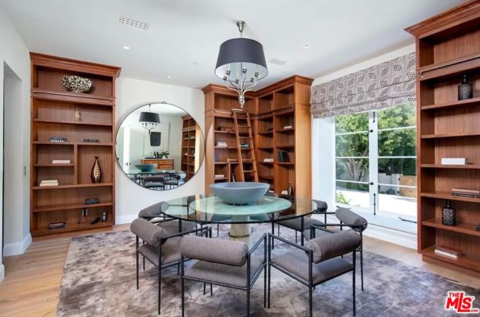 """Yet another dining room featuring wood shelving and a round, glass table. <br><br> *Image by [MLS/Zillow](https://www.zillow.com/homedetails/8-Beverly-Park-Beverly-Hills-CA-90210/20533668_zpid/?